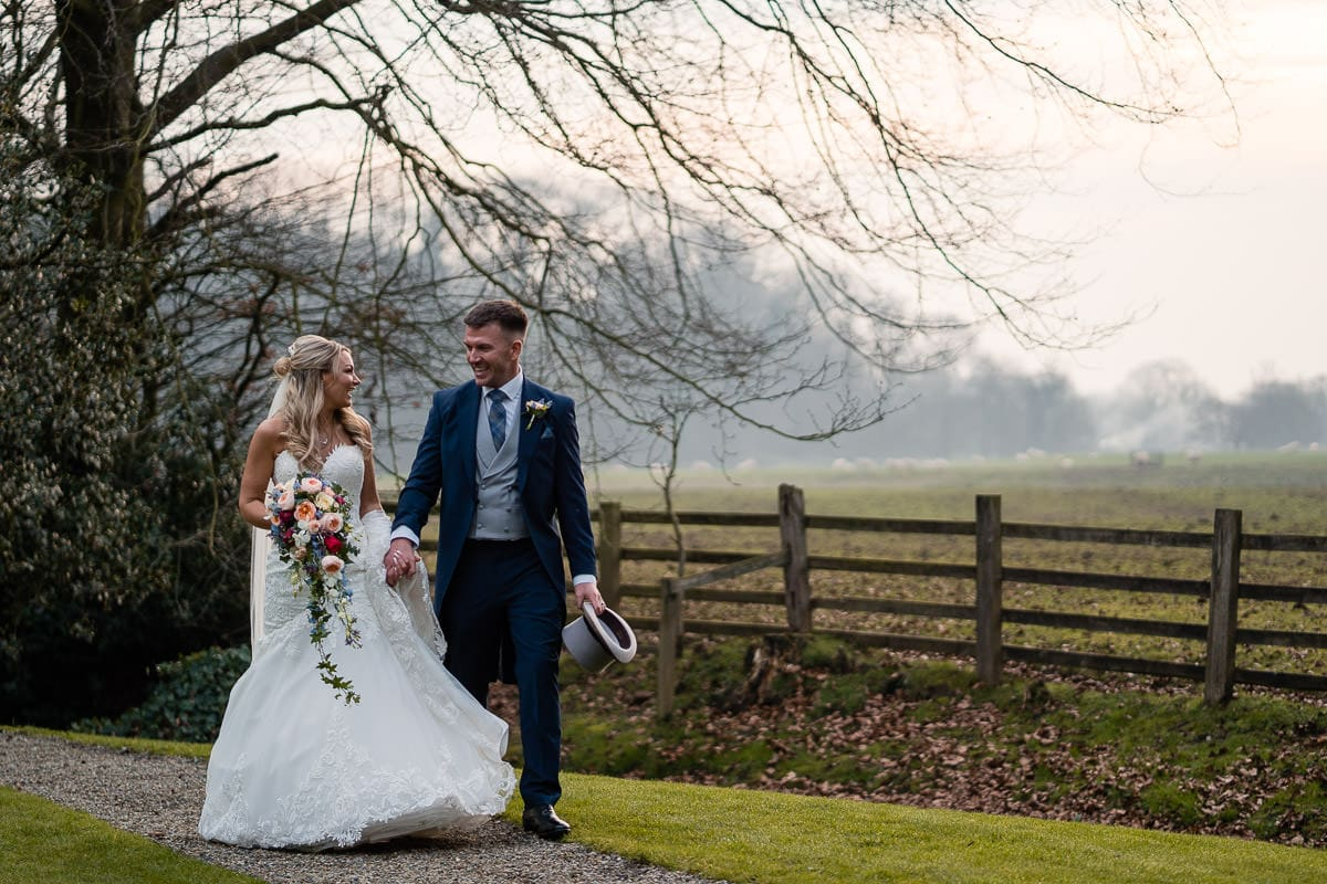 bride and groom walking at mitton hall