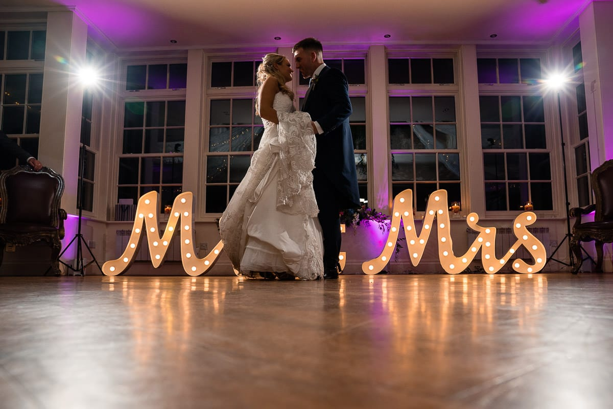 first wedding dance in front of light up mr and mrs sign