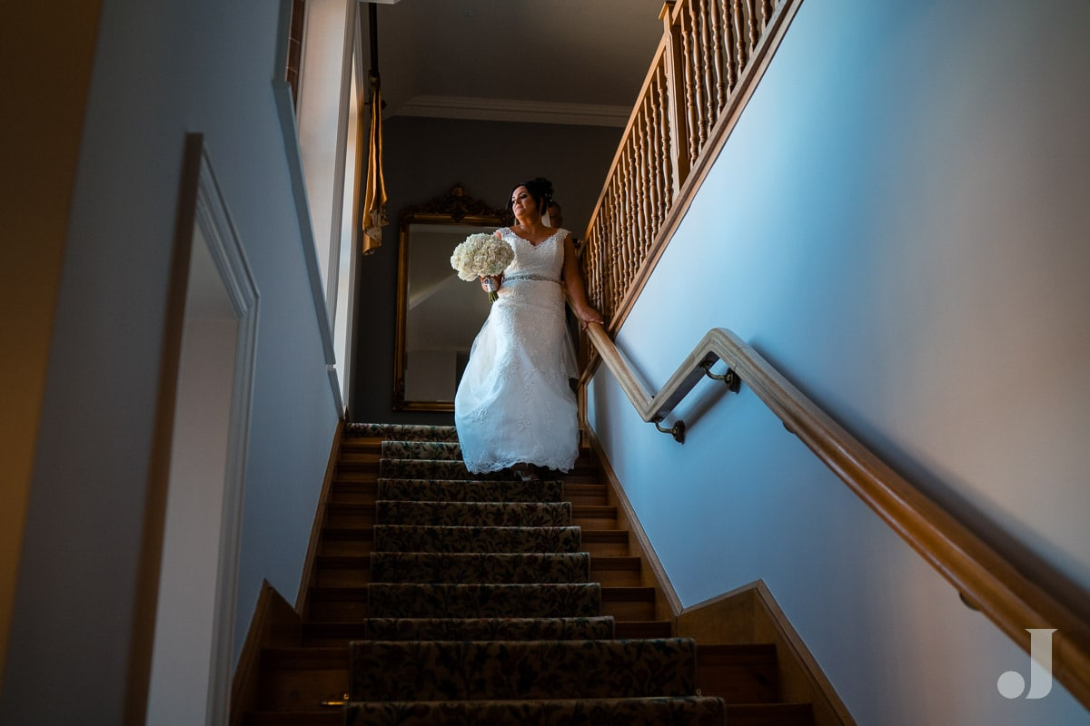 bride walking down staircase at Colshaw Hall