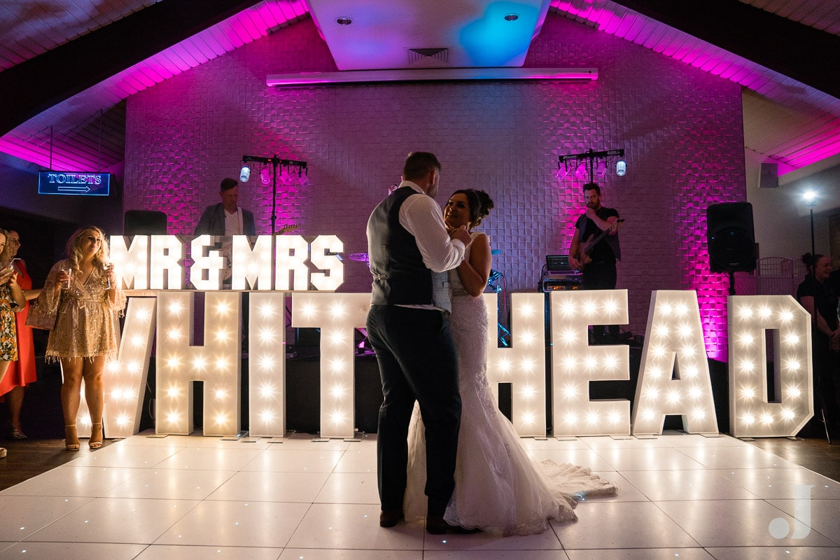 first dance in front of light up letters