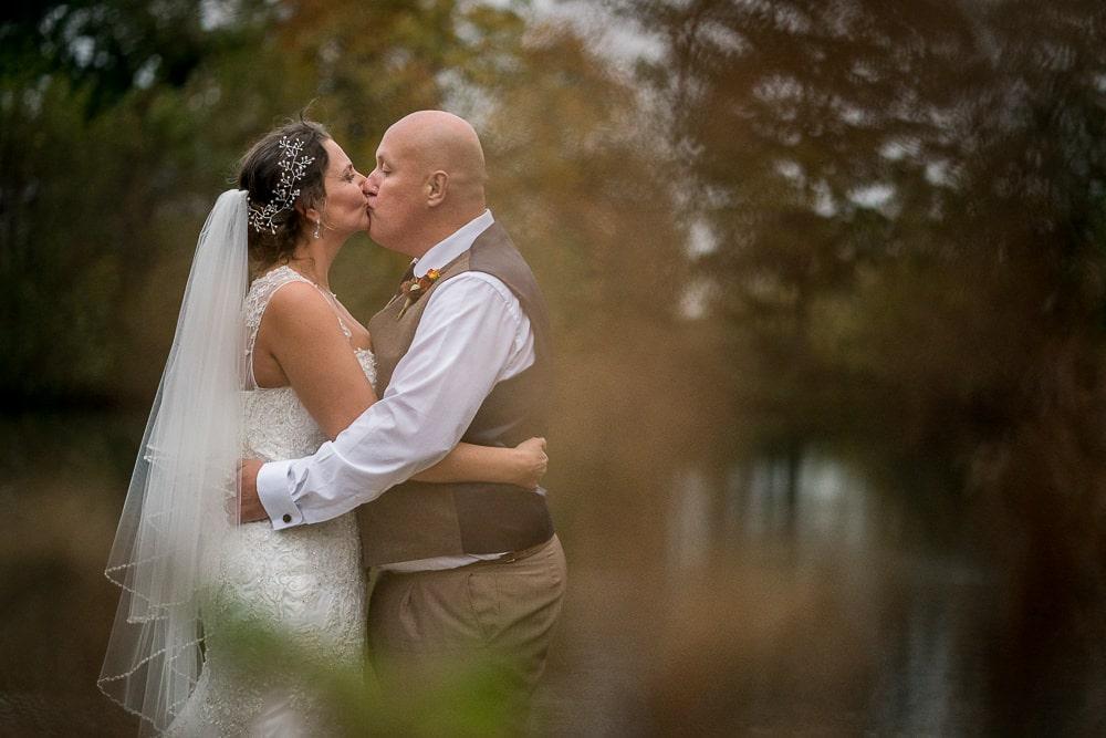 couple kissing on lake at styal lodge