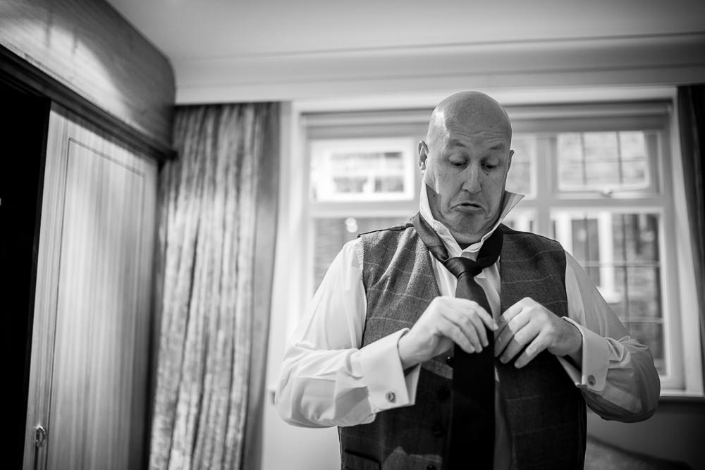 groom putting his tie on