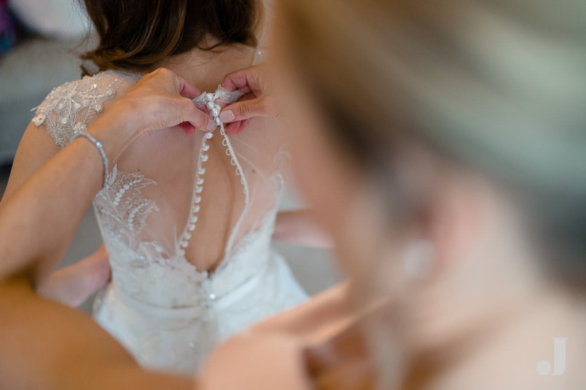bride being buttoned into her wedding dress