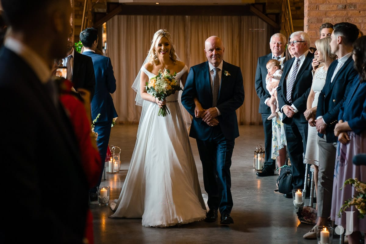 bride walking up the aisle at the holford estate
